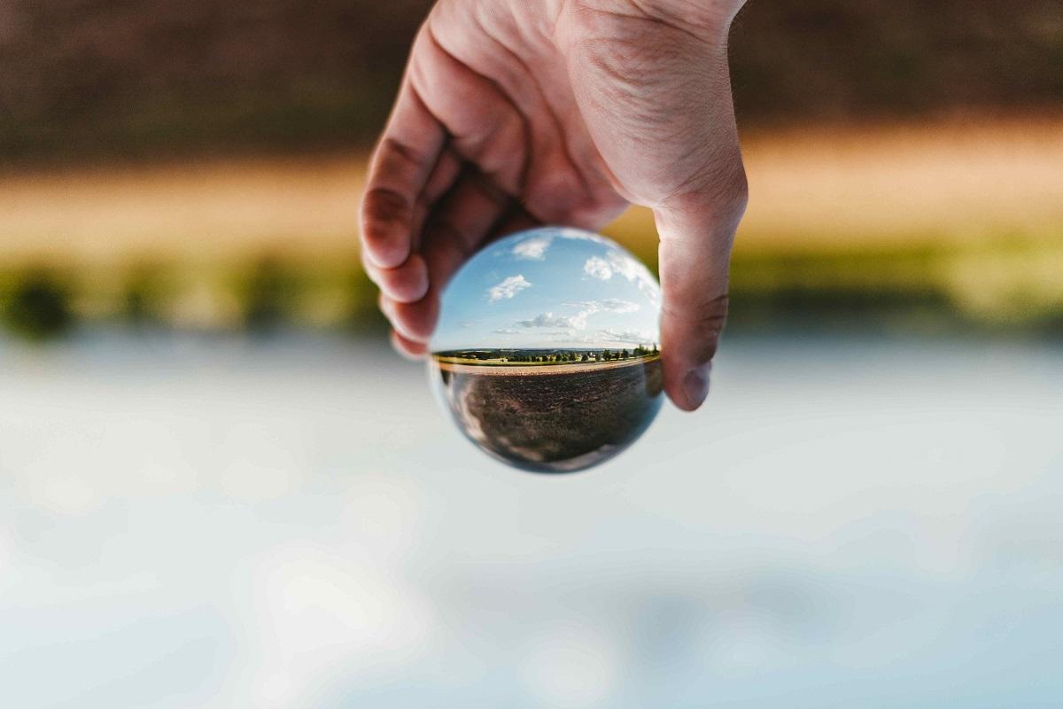 Foto von einer Hand, die über dem Meer eine Glaskugel hält, durch die eine Landschaft und den Himmel gesehen werden können
