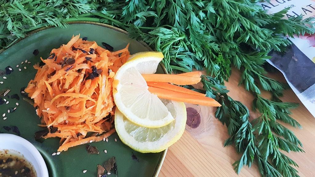 Foto vom Möhrensalat mit Zitronenscheiben und Grünem auf einem Teller