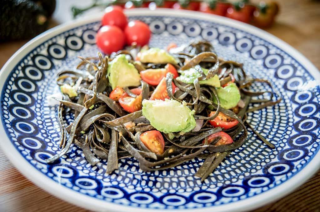 Foto eines Tellers mit Algenpasta mit Avocado und Tomaten