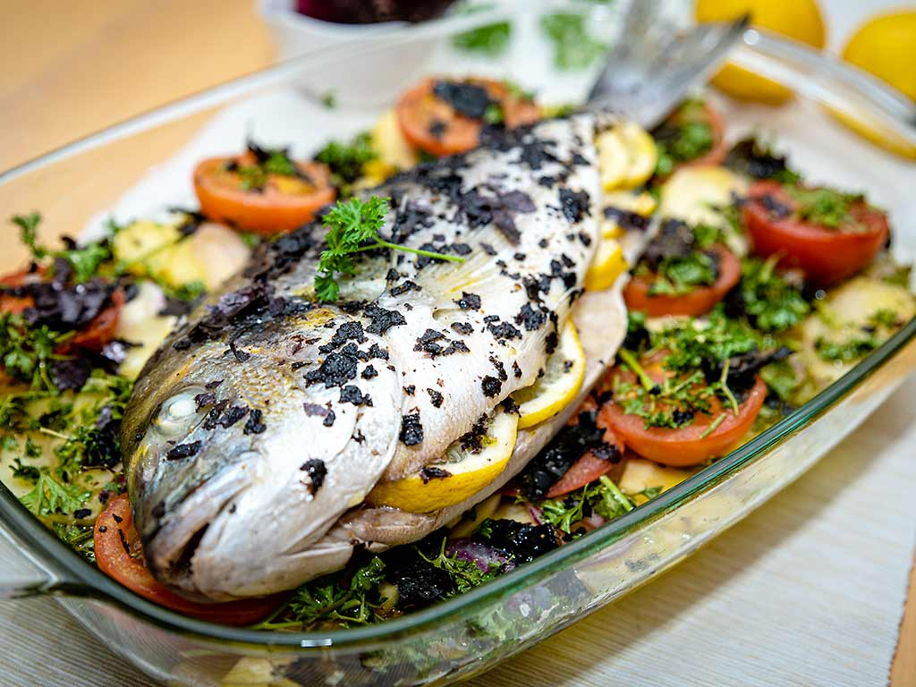 Foto einer im Ofen gebackenen Dorade auf Gemüse mit Algen